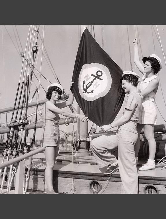 Three women raising harbor flag