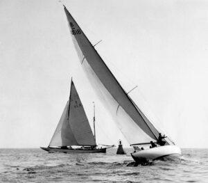 Two 8 Metre racing sloops rounding a mark.