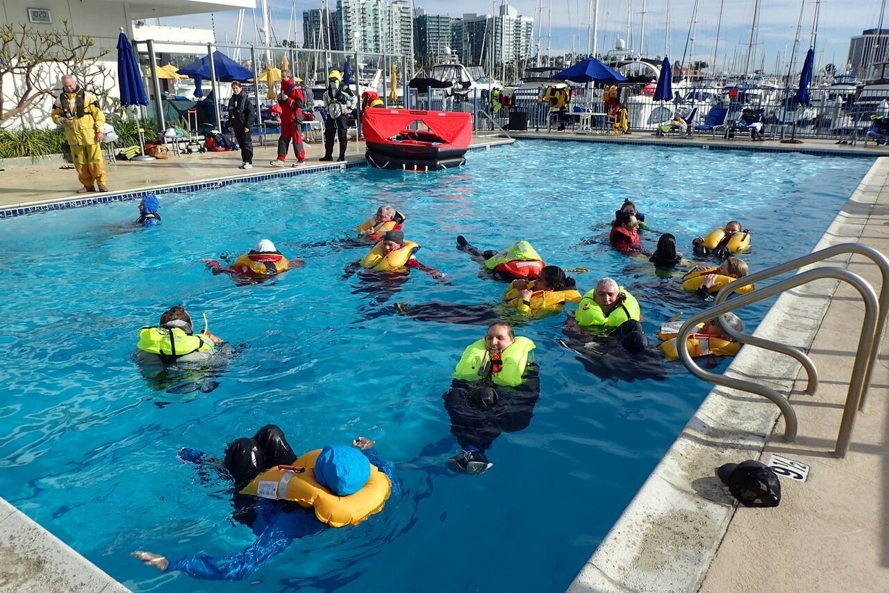 people in a pool wearing inflatable life jackets